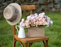 Basket with flowers. On a chair with a hat in spring Stock Photography