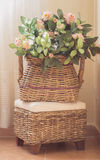 Basket of flowers. In the corner of a house. Toned image Royalty Free Stock Photo