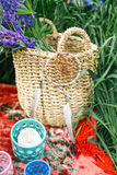 Basket with flowers and dream catcher on red blanket Stock Photos