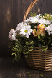Basket of flowers. Over grunge wooden background Royalty Free Stock Photography