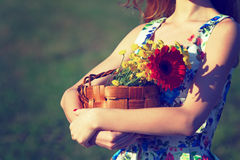 Basket of flowers.Photo toned in retro style. Abstract photo of a young girl with a basket of flowers Royalty Free Stock Photo