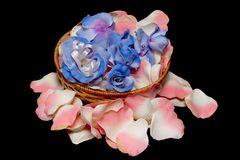 Basket with flowers on rose textile petals Royalty Free Stock Image