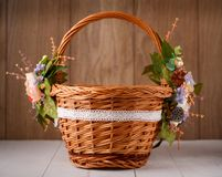 Basket with flowers to celebrate Easter on a wooden background Stock Photos