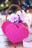 Basket with flowers and two hearts Stock Photo
