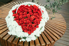 Basket of flowers on wooden bench. heart shape of red roses Stock Photo