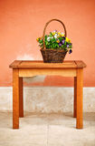 Basket with flowers on wooden table Stock Photo