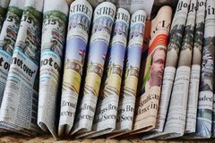 A basket of folded English language newspapers Stock Images