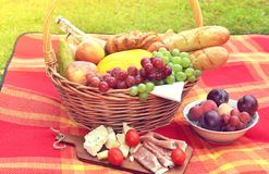 Basket with Food Fruit Bakery Cheese Ham Tomato Picnic Green Grass Toned Photo. Basket with Food Fruit Bakery Cheese Ham Tomato Picnic Green Grass Summer Time royalty free stock photo