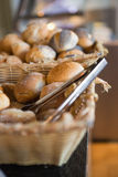 Basket with fresh bread and tongs Stock Photo