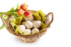Basket with fresh chicken eggs and red tulips for a Happy Easter stock images