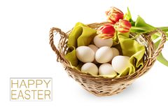 Basket with fresh chicken eggs and red tulips for a holiday breakfast, text happy easter, isolated on a white background, copy s stock photo