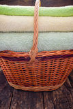 Basket with fresh clean colorful towels on a wooden Stock Photos
