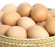 Basket of fresh eggs. Pile of fresh eggs in basket with white background Stock Image