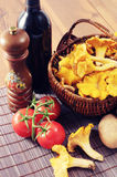 Basket with fresh golden chanterelles and potatos tomatos and re. D wine on table. cooking ingredients Stock Photos