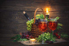 Basket with fresh grapes and a glass of wine on a wooden table. Autumn background. Harvest Royalty Free Stock Photos