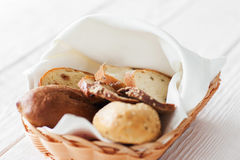 Basket with fresh hot bread on white wooden table Royalty Free Stock Photo