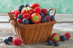 Basket with fresh juicy berries on a wooden table, close-up Royalty Free Stock Images