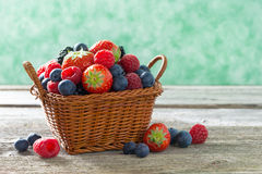 Basket with fresh juicy berries on a wooden table. Horizontal Royalty Free Stock Images