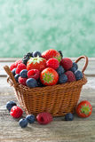 Basket with fresh juicy berries on a wooden table, vertical Stock Images