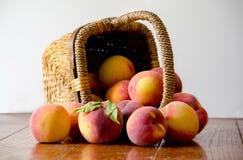 Basket of fresh peaches on white Stock Photo