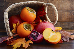 Basket of fresh persimmons and pomegranates Royalty Free Stock Photography