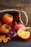 Basket of fresh persimmons and pomegranates Royalty Free Stock Photo
