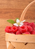 Basket with fresh raspberries. Against wooden background Stock Photos