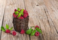 Basket with fresh raspberries. Raspberries with leaves in a basket  on a wooden board with copy-space Royalty Free Stock Photos