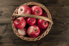 Basket of fresh ripe apples on wooden background. Stock Photos