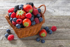 Basket of fresh seasonal berries on wooden table, top view. Horizontal Royalty Free Stock Images