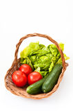 Basket of fresh vegetables. Wicker basket with green salad, tomatoes and cucumbers for a salad Royalty Free Stock Images
