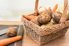 Basket of Fresh Vegetables. A Basket of Fresh Vegetables displayed on a wooden background with chopping board Stock Photography
