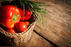 Basket of fresh vegetables on rustic wooden table Stock Photography