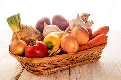 Basket with fresh vegetables on wihte rustic table. Ingredients to make a vegetable soup, onion, carrot, garlic, potato, turnip, tomato, paprika, celery in a Stock Image