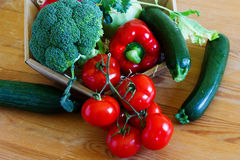 Basket with fresh vegetables on a wooden table Stock Photos
