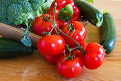 Basket with fresh vegetables on a wooden table Royalty Free Stock Images