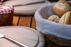 Basket of freshly baked dinner rolls with tableware in background. Macro. Basket of freshly baked dinner rolls with tableware in background. close up Royalty Free Stock Images
