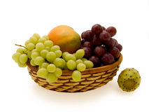 Basket with fruit. Bright fruit of a mango in a basket with green and purple grapes; near to a basket a fruit of a cactus Stock Photo