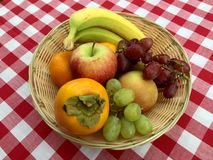 Basket of fruit. A basket of fresh fruit on a gingham tablecloth Stock Photo