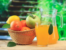 Basket of fruit and juice. On a wooden table in the garden Stock Photos