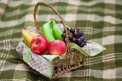 Basket with fruits. Basket with different fruits on the checked plaid Stock Image