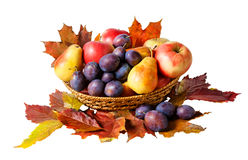 Basket with fruits and autumn leaves isolated on white Stock Photo