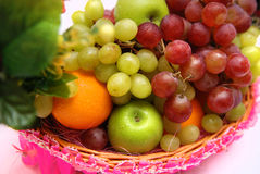 Basket of fruits. Basket with decoration contains grapes, green apple, oranges Royalty Free Stock Images