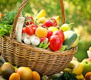 Basket with fruits and vegetables close-up. Wicker basket is full with fresh fruits and vegetables stock image