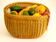 Basket with Fruits. Wicker Basket with Bananas, Oranges, Apples, Lemon and Avocado in white Background Stock Photos