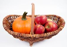 Basket full of apples and a pumpkin. On a white background royalty free stock images