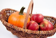 Basket full of apples and a pumpkin. On a white background stock image
