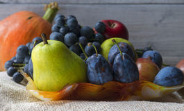 Basket full of autumn fruits and orange pumpkin Royalty Free Stock Photography
