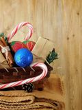 Basket full of Christmas attributes and present boxes on a plaid on a wooden background Royalty Free Stock Image