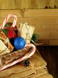 Basket full of Christmas attributes and present boxes on a plaid on a wooden background Stock Photography